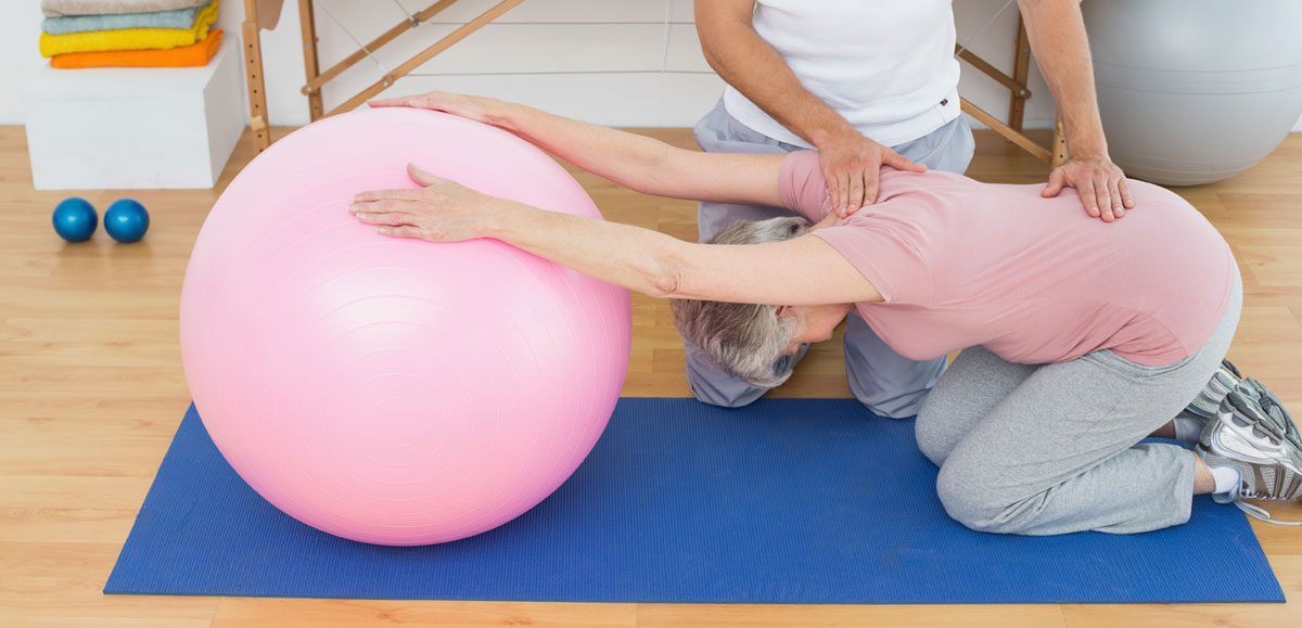 Physical_therapist_assisting_senior_woman_with_yoga_ball1